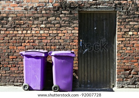 Refuse bins against old brick wall