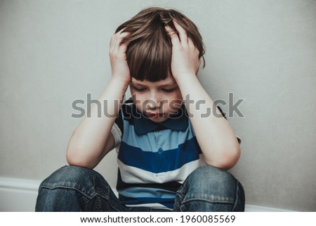 Regret sad little boy sitting alone loneliness,stressed depressed child crying having depression, anxiety, trouble of mental health, lonely kid boy with hands on head, Hikikomori Syndrome Disease Stockfoto ©
