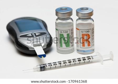 Regular and NPH insulin with glucometer and insulin syringe. - stock photo