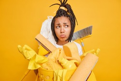 Regular clean up concept. Frustrated overworked housemaid spreads hands stands sad surrounded by cleaning tools busy doing domestic chores isolated over yellow background. Discontent housekeeper