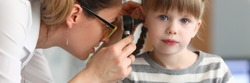 Regular pediatric medical examination at doctor. Female ENT wears glasses and jewelry, she examines ear small patient with special device. Girl sits quietly on couch and awaits end procedure.