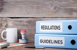 Regulations and Guidelines. Two binders on desk in the office. Business background