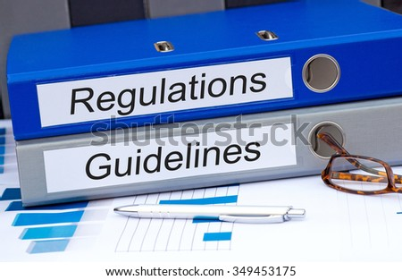 Regulations and Guidelines - two binders with text on desk in the office #349453175