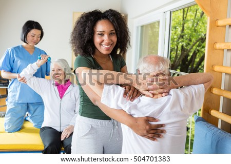 Rehab clinic for elder people. Asian and african nurse following old patients.