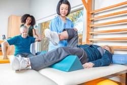 Rehab clinic gym. Multi racial nurses helping elder patients.