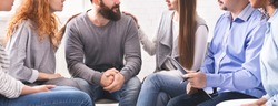 Rehab group meeting. Women comforting stressed man at support therapy, panorama