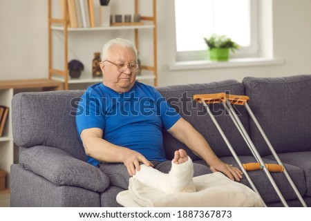 Rehabilitation after domestic or car accident injury: Senior male stays at home, waiting for bone fracture to heal. Old man with broken leg in plaster cast sitting on sofa with crutches in living-room Сток-фото ©