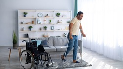 Rehabilitation concept. Young black guy walking with crutches after using wheelchair at home, panorama