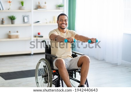 Rehabilitation of disabled people. Young African American man in wheelchair working out at home ストックフォト ©