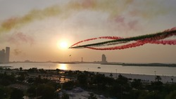 rehearsal air show in prior to UAE national day 2020. 7 jet planes flying along corniche Rd. in Abu Dhabi paint the sky with UAE flag colour.