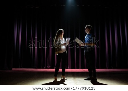 Rehearsal at theatre. Man explain to student actress how to play on the stage on the new performance for public. Dark hall at background. Stock fotó ©