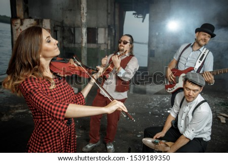 Rehearsal of rock and roll band. Guitarist, bass guitarist, drummer, violinist and soloist in stage costumes