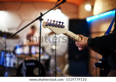 Rehearsal of rock musicians before a concert in a music studio. Photo of electric guitar neck with musician's hand and microphone stand. In the background a blurred studio with a drummer and drum kit. #1519779110