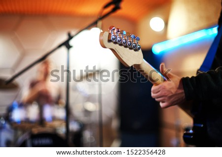 Rehearsal of rock musicians before a concert in a music studio. Photo of electric guitar neck with musician's hand and microphone stand. In the background a blurred studio with a drummer and drum kit. #1522356428