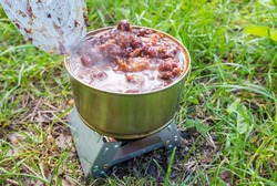 Reheating canned beans with meat on a tourist stove with dry fuel on a camping trip, hiking food concept.