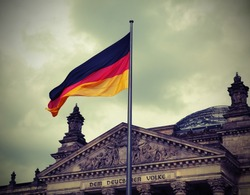 Reichstag building is Parliament of Germany in Berlin city with big flag. The dedication text  over the main entrance DEM DEUTSCHEN VOLKE meaning To the German People. Vintage Effect