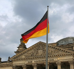 Reichstag building is Parliament of Germany in Berlin with flag. The text  over the main entrance DEM DEUTSCHEN VOLKE meaning To the German People