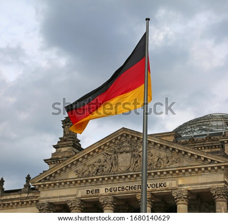 Reichstag building is Parliament of Germany in Berlin with flag. The text  over the main entrance DEM DEUTSCHEN VOLKE meaning To the German People Foto d'archivio ©