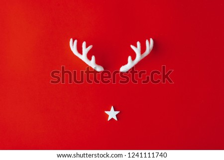 Reindeer antlers with star on red background. Christmas minimal Greeting card. #1241111740