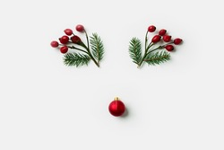 Reindeer face made of Christmas decorations, holly berries and pine branches. Minimal  concept. Flat lay