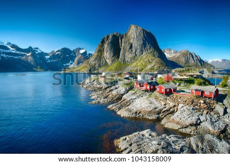Photo of  Reine, Lofoten, Norway - 04/06/2017:  The village of Reine under a sunny, blue sky, with the typical red rorbu houses.