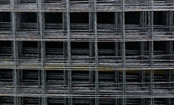 Reinforcement mesh is stacked for use in reinforced concrete construction work. Steel material in the form of a metal mesh for strengthening the wall, floor, floor and foundation. Abstract background.