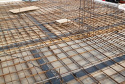 reinforcement of concrete with metal rods connected by wire. view of wooden formwork with metal holders, which will be filled with overlap between floors in country house under construction from block