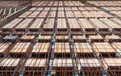 reinforcement of concrete with metal rods connected by wire. view of wooden formwork with metal holders on which the concrete will be laid