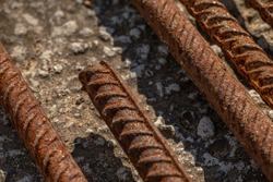 Reinforcement on a concrete surface. Rusty fittings. Reinforcing bars on a concrete floor.
