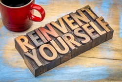reinvent yourself - motivational words in vintage letterpress wood type against grunge, painted wood with a cup of coffee