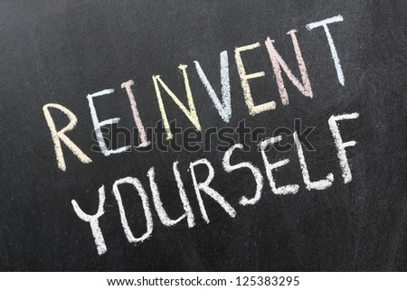 reinvent yourself phrase handwritten on school blackboard