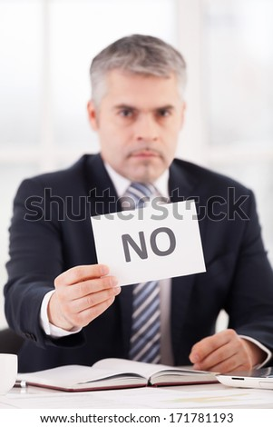 Rejected! Confident senior man in formalwear holding a paper with no sign on it while sitting at her working place