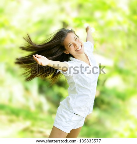 Rejoicing happy woman in flying motion smiling full of joy and vitality in summer or spring forest. Eurasian female model.