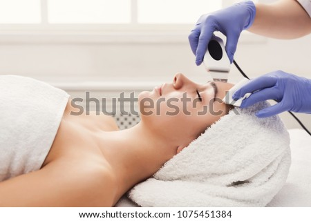 Rejuvenating facial treatment. Model getting lifting therapy massage in a beauty SPA salon. Exfoliation, stimulation and hydratation. Aesthetic cosmetology, closeup, copy space, side view Foto stock ©