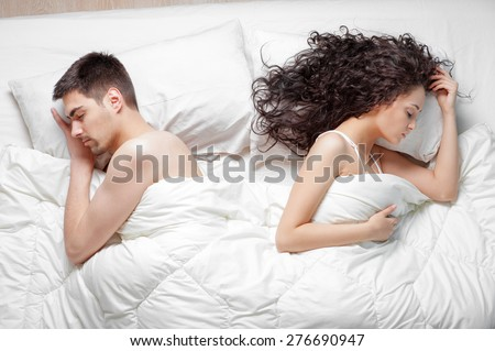 Relationship concept. Top view of young couple lying on the bed.
