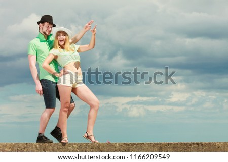 Relationship concept. Young hipster couple in love against sky. Best friends sharing free time looking up showing with finger outdoor #1166209549