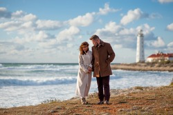 relationship concept young man and woman in autumn coat walking along stormy sea coast with lighthouse