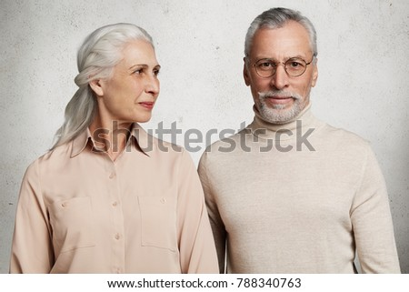 Relationship, old age and people concept. Senior couple spend time together at home, wait for children, pose against white concrete wall. Bearded elederly man in spectacles and his affectionate wife #788340763