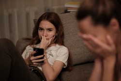 Relationship problems between teenagers and their parents. True emotions. Tired and unhappy mother worried about her rebellious daughter and upset that she spends a lot of time on  mobile phone.