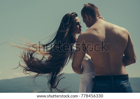 Shutterstock Relationship, romance concept. Couple in love on blue sky. Summer vacation, wanderlust. Man hug woman with long hair on sunny day. Girl and macho with muscular torso on nature.