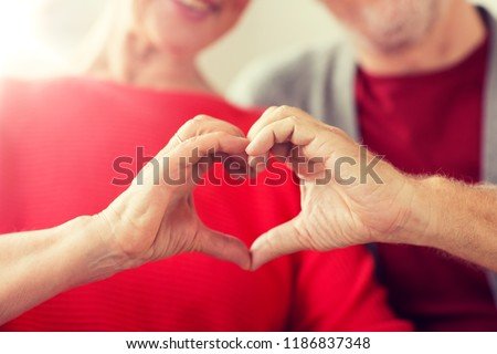 relationships, love and old people concept - close up of senior couple showing hand heart gesture