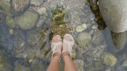 Relax and holiday time. A woman take her foot in the river water at Kiriwong village, Nakhon si thammarat city, Thailand.