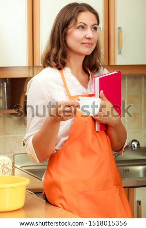 Relax and rest in kitchen. Middle aged woman chef housekeeper holding cookbook with cup of tea coffee. Housewife resting at home.