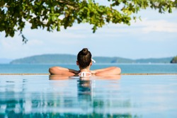 Relax and spa concept. Woman with a flower in hair relaxing in a pool towards the sea  at Krabi, Thailand.