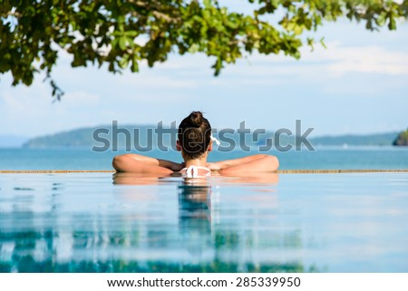 Relax and spa concept. Woman with a flower in hair relaxing in a pool towards the sea \ at Krabi, Thailand.