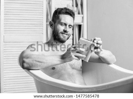 Relax at home. Total relaxation. Personal hygiene. Nervous system benefit bathing. Relax concept. Man muscular torso relax bathtub and read book. Relaxed guy reading book while relaxing in hot bath.