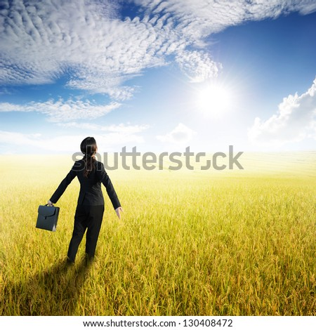 Relax business woman holding bag in yellow rice field and sun sky