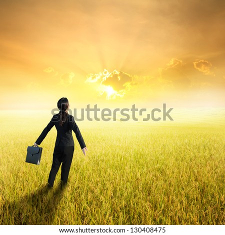 Relax business woman holding bag in yellow rice field and sunset