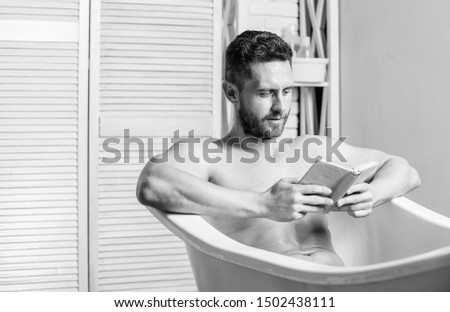 Relax concept. Man muscular torso relax bathtub and read book. Relaxed guy reading book while relaxing in hot bath. Relax at home. Total relaxation. Personal hygiene. Nervous system benefit bathing.