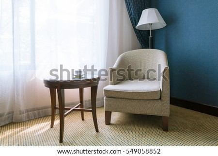 relax concept : vintage chair, cup of tea on wooden table with Lamp on deserted old carpet floor.